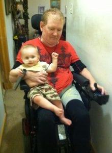 Papa giving Eli a ride on the wheelchair