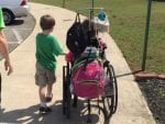 Children using handicap accessible sidewalk for stroll with attached medication supplies.