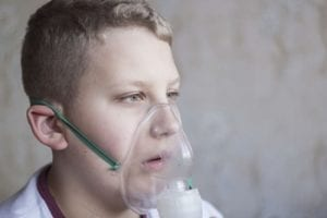 Boy wearing face mask delivering oxygen therapy.