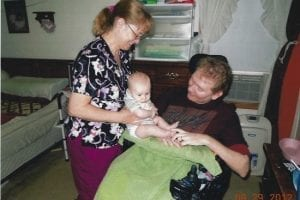 Family Caregiver helping spouse enjoy time with grandchild