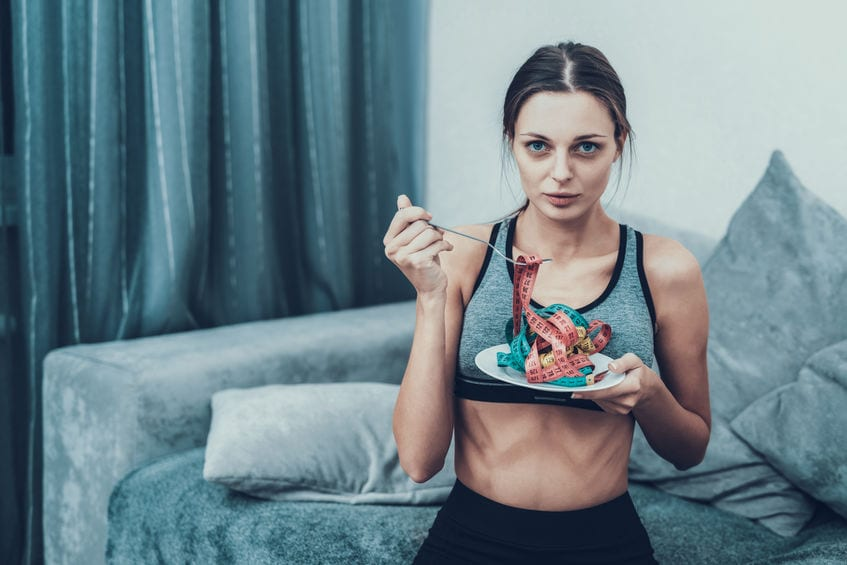 Woman with eating disorder (Anorexia) holding plate with tape measure showing her life is focused on her weight not on what she eats.