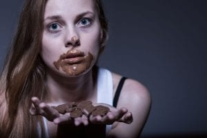 Binge Eating chocolate cake until it's all gone even though she doesn't want it.
