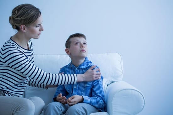 Young child with autism spectrum disorder looking away from mother trying to talk to him.