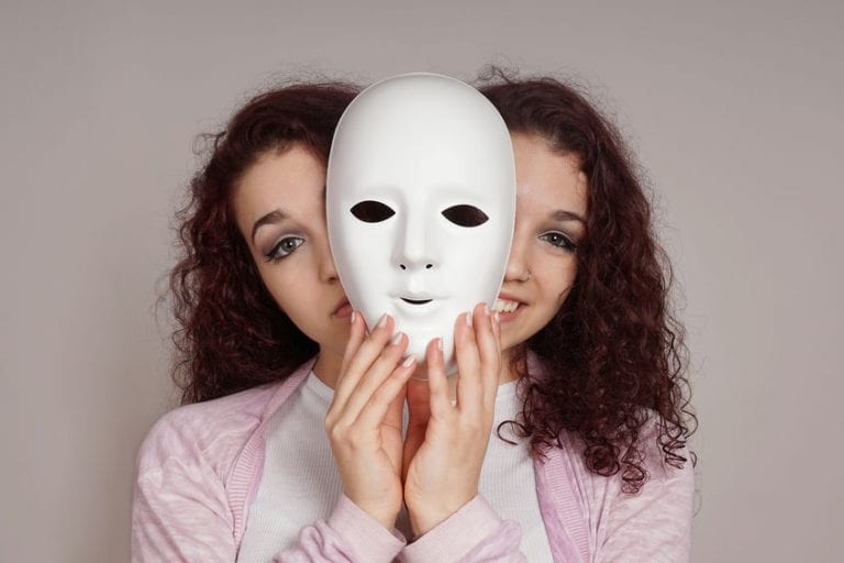 Woman with bipolar mental health disorder feels like she is two people inside-both happy and sad unsure which feeling is appropriate for the situation.