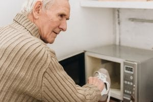 Senior man with Alzheimer's disease putting shoe in microwave oven.